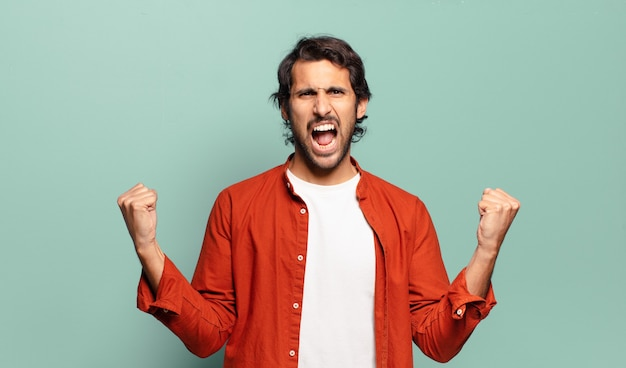 Giovane uomo indiano bello che grida in modo aggressivo con un'espressione arrabbiata o con i pugni chiusi per celebrare il successo