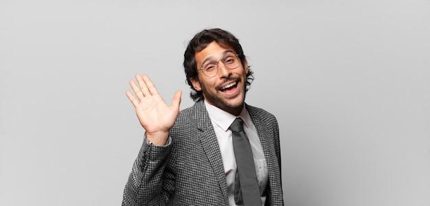 Giovane bell'uomo indiano che sorride allegramente e allegramente, agitando la mano, accogliendoti e salutandoti, o salutandoti. concetto di business