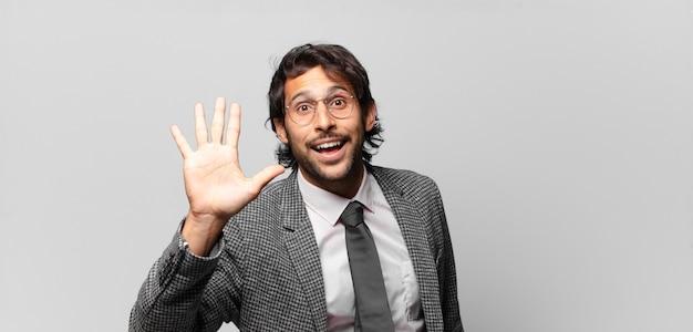 Giovane uomo indiano bello che sorride e sembra amichevole, mostrando il numero cinque o il quinto con la mano in avanti, conto alla rovescia