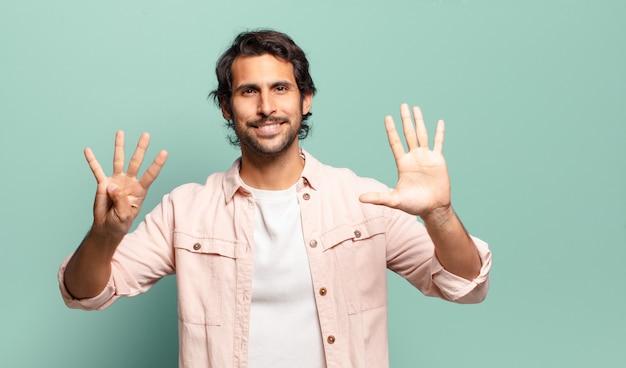 Giovane uomo indiano bello che sorride e che sembra amichevole, mostrando il numero nove o nono con la mano in avanti, conto alla rovescia