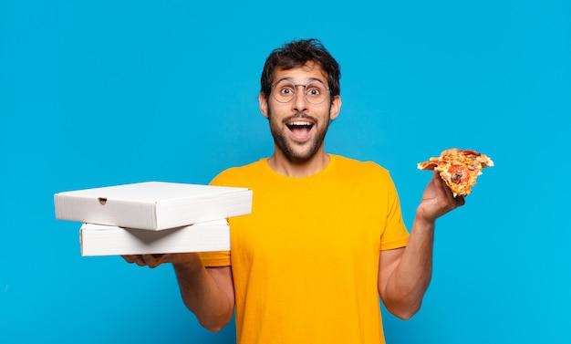 Il giovane uomo indiano bello ha sorpreso l'espressione e tiene le pizze da asporto