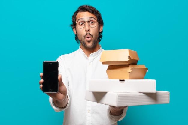 Il giovane uomo indiano bello porta via il concetto di fast food