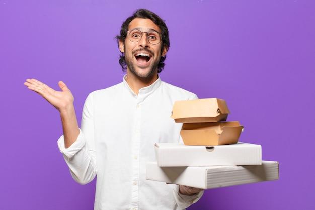 Il giovane uomo indiano bello porta via il concetto degli alimenti a rapida preparazione
