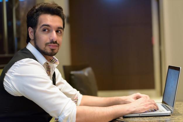 Bel giovane uomo indiano utilizzando laptop guardando indietro nella hall dell'hotel
