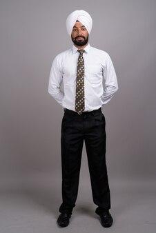 Giovane uomo d'affari indiano bello sikh che indossa turbante su grigio