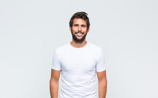 Giovane uomo latino bello in posa e guardando alla telecamera contro il muro bianco