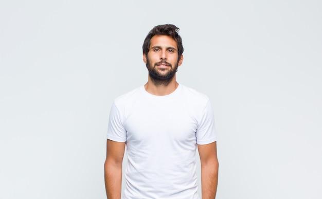Giovane uomo latino bello in posa e guardando davanti contro il muro bianco