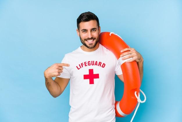 Il giovane uomo bello del bagnino isola la persona che indica a mano uno spazio della copia della camicia, fiero e sicuro