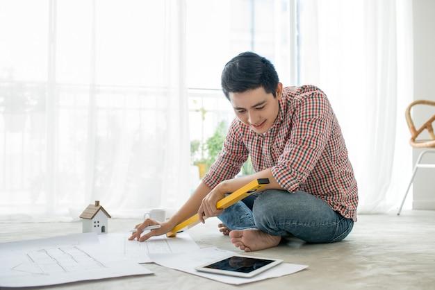 Giovane architetto asiatico maschio bello che lavora a casa sul pavimento.