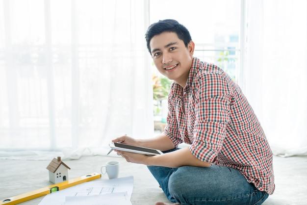 Giovane architetto asiatico maschio bello che lavora a casa facendo uso della compressa sul pavimento.