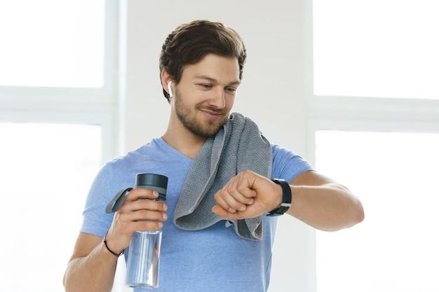Uomo giovane e bello dopo l'allenamento fitness nella palestra luminosa