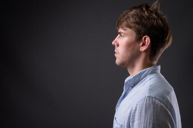 Giovane uomo bello contro il muro grigio