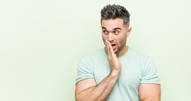 Il giovane uomo bello contro uno sfondo verde sta dicendo una notizia segreta di frenata calda e sta guardando da parte