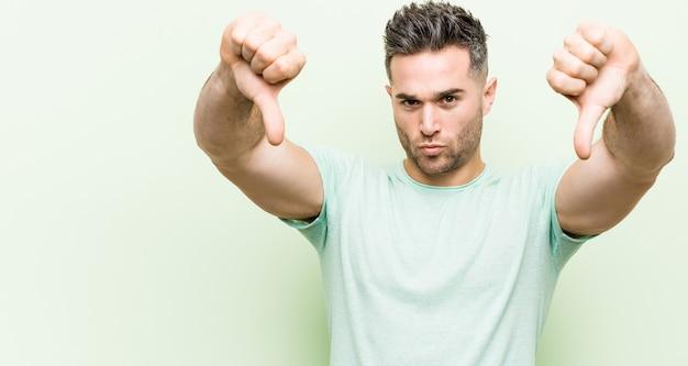 Giovane uomo bello contro uno sfondo verde che mostra il pollice verso il basso ed esprime antipatia.