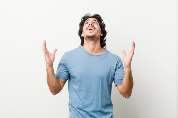 Giovane uomo bello contro uno spazio bianco che grida al cielo, alzando lo sguardo, frustrato.