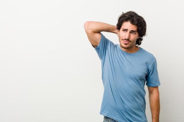 Giovane uomo bello contro un muro bianco toccando la parte posteriore della testa, pensando e facendo una scelta.