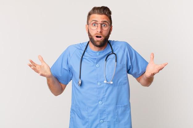 Giovane bell'uomo stupito, scioccato e stupito con un'incredibile sorpresa. concetto di infermiera