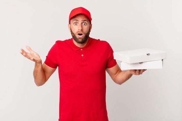 Giovane bell'uomo stupito, scioccato e stupito con un'incredibile sorpresa. concetto di consegna della pizza