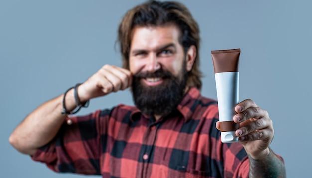 Giovane uomo bello che applica lozione crema. l'uomo tiene la bottiglia nera di shampoo o gel doccia. shampoo balsamo per uomo. cura esperta per capelli esigenti. contenitore di plastica con shampoo.