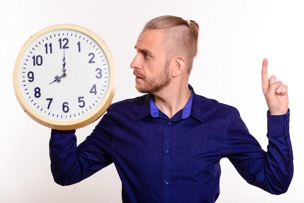 Giovane uomo bello in camicia blu guarda il grande orologio in piedi rivolto verso l'alto su bianco