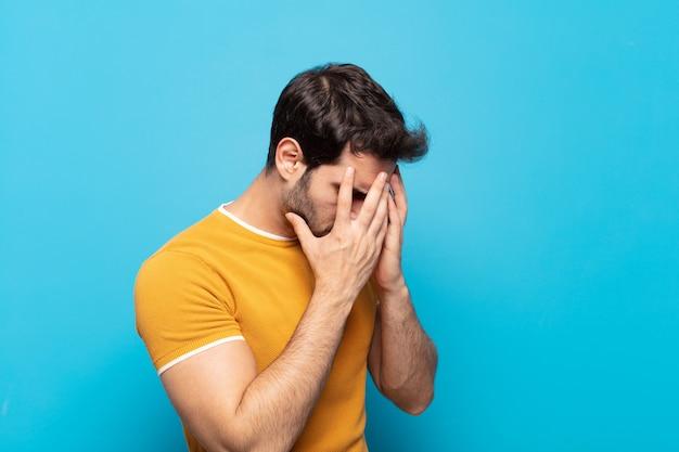 Giovane uomo bello che copre gli occhi con le mani con uno sguardo triste e frustrato di disperazione, pianto, vista laterale