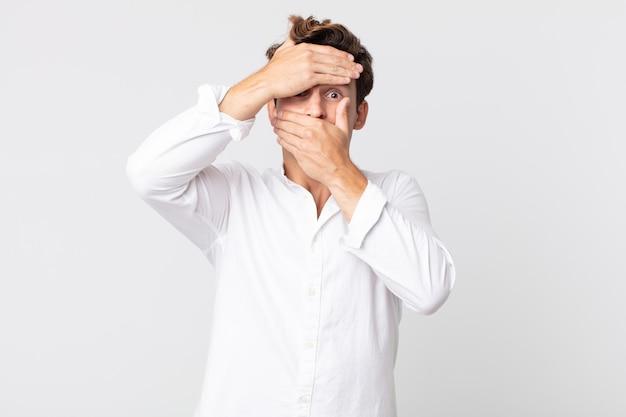 Giovane uomo bello che copre il viso con entrambe le mani dicendo no alla telecamera! rifiutare le foto o vietare le foto
