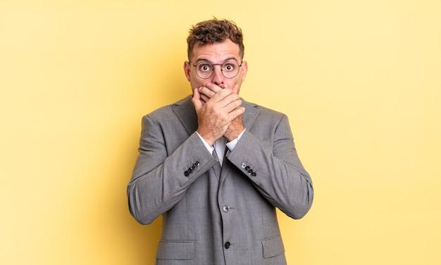 Giovane uomo bello che copre la bocca con le mani con uno scioccato. concetto di business