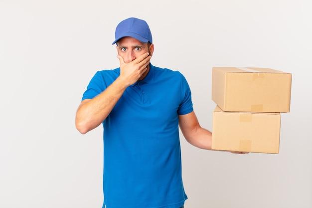 Giovane uomo bello che copre la bocca con le mani con uno scioccato. concetto di consegna del pacchetto