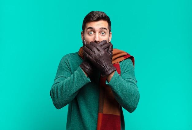 Giovane uomo bello che copre la bocca con le mani con un'espressione scioccata e sorpresa, mantenendo un segreto o dicendo oops. concetto di freddo e inverno