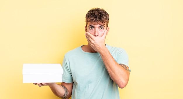 Giovane uomo bello che copre la bocca con le mani con uno scioccato. concetto di scatola bianca