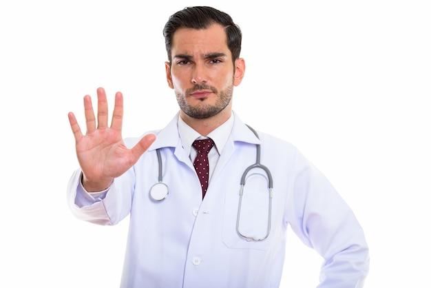 Giovane medico bello che mostra il segno della mano di arresto