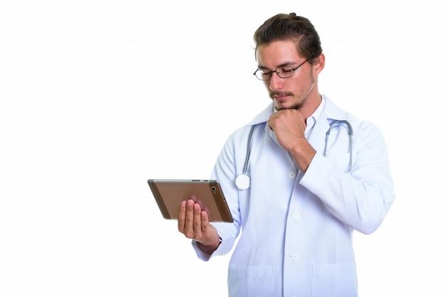 Giovane medico bello dell'uomo che per mezzo della compressa digitale