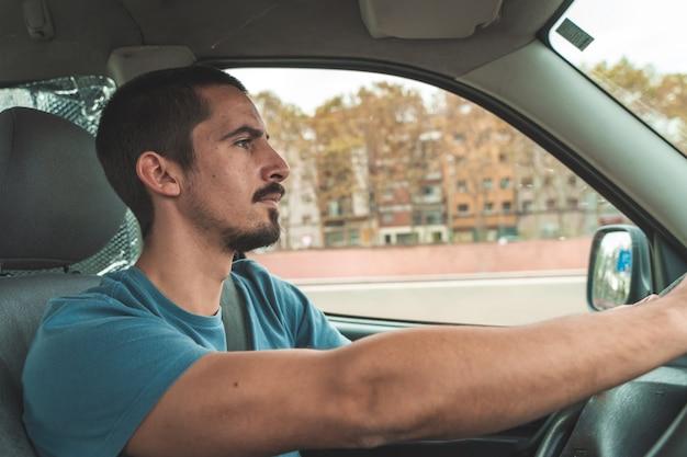 Giovane bell'uomo alla guida di un'auto trasporto e concetto di veicolo