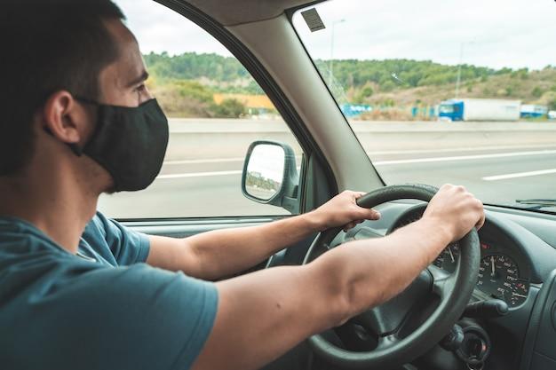 Giovane bell'uomo alla guida di un'auto con maschera chirurgica per prevenire il concetto pandemico di coronavirus