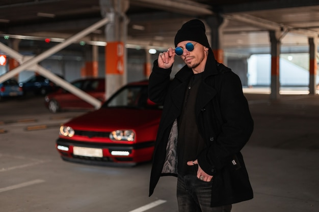 Giovane bell'uomo in abiti alla moda con un cappotto nero e un cappello che si aggiusta i suoi occhiali da sole vintage sullo sfondo di un'auto rossa al parcheggio