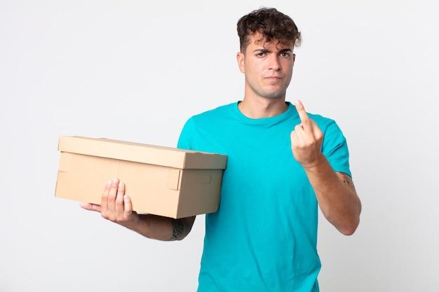 Giovane bell'uomo che si sente arrabbiato, infastidito, ribelle e aggressivo e tiene in mano una scatola di cartone