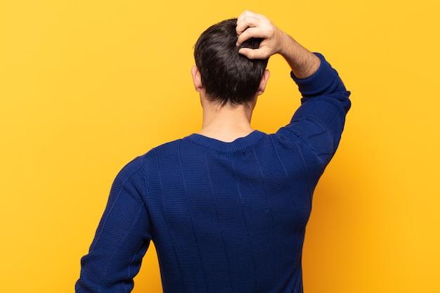 Giovane uomo bello sentirsi all'oscuro e confuso, pensando a una soluzione, con una mano sull'anca e l'altra sulla testa, vista posteriore