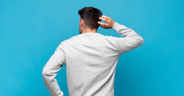 Giovane uomo bello che si sente incapace e confuso, pensando a una soluzione, con una mano sull'anca e l'altra sulla testa, vista posteriore