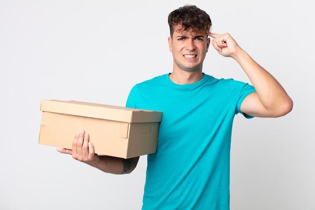 Giovane bell'uomo che si sente confuso e perplesso, mostra che sei pazzo e tiene in mano una scatola di cartone