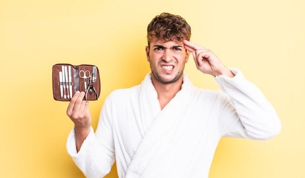 Giovane bell'uomo che si sente confuso e perplesso, mostrando che sei pazzo. concetto di custodia per attrezzi per unghie