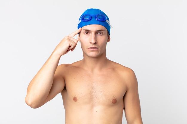 Giovane bell'uomo che si sente confuso e perplesso, mostrando che sei pazzo. concetto di nuotatore
