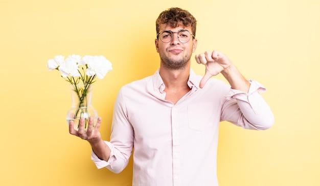 Giovane bell'uomo che si sente arrabbiato, mostra i pollici in giù. concetto di fiori