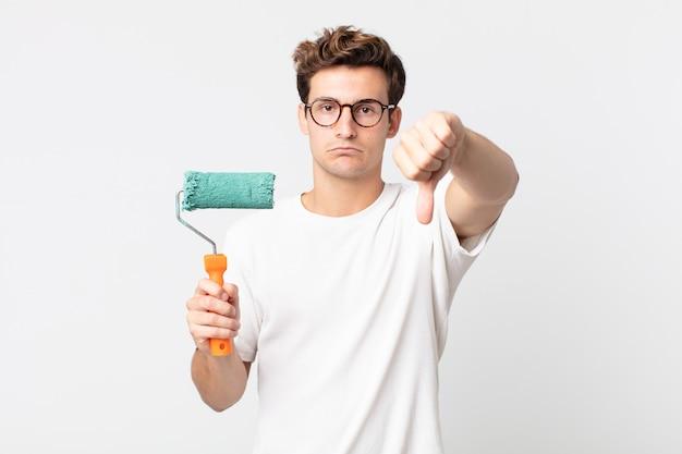 Giovane bell'uomo che si sente arrabbiato, mostra i pollici in giù e tiene in mano una vernice a rullo