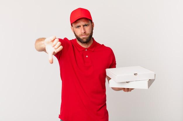 Giovane bell'uomo che si sente arrabbiato, mostra i pollici in giù. concetto di consegna della pizza