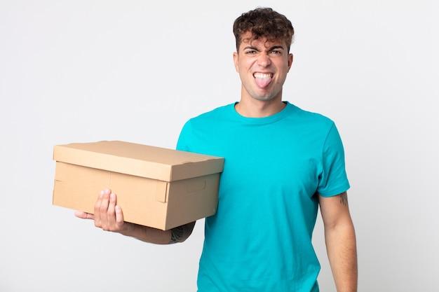 Giovane bell'uomo che si sente disgustato e irritato e fa la linguaccia e tiene in mano una scatola di cartone