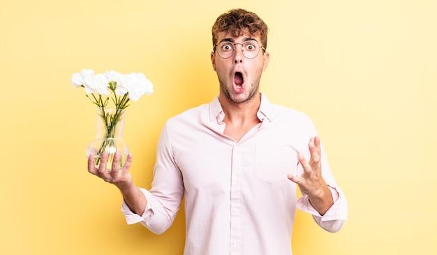 Giovane bell'uomo che si sente estremamente scioccato e sorpreso. concetto di fiori