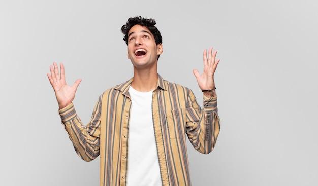 Giovane uomo bello che si sente felice, stupito, fortunato e sorpreso, celebrando la vittoria con entrambe le mani in aria