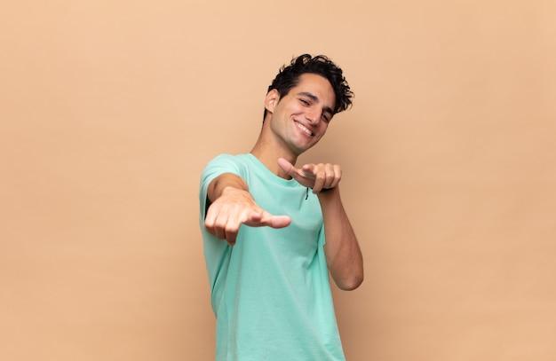 Giovane bell'uomo che si sente felice e fiducioso, indicando la telecamera con entrambe le mani e ridendo, scegliendo te