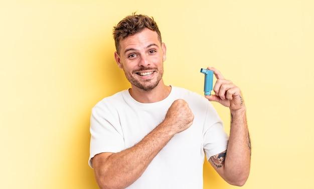 Giovane uomo bello sentirsi felice e affrontare una sfida o festeggiare. concetto di asma