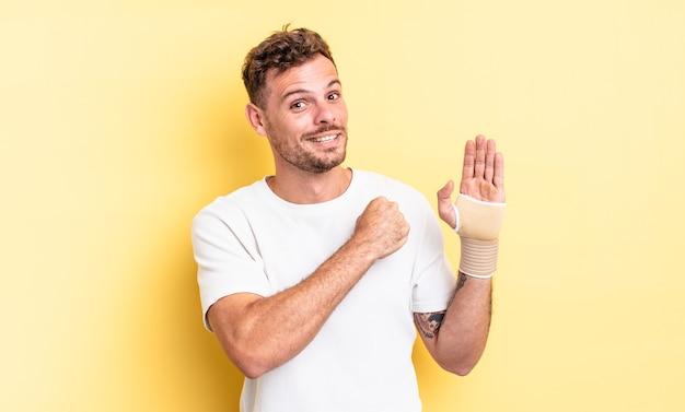 Giovane uomo bello sentirsi felice e affrontare una sfida o festeggiare. concetto di fasciatura per le mani